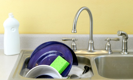 Washing dishes: Dishes in soapy water in a sink with dish soap on the side