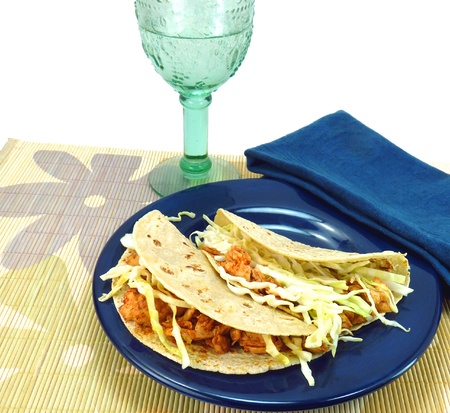 Two fish tacos made with corn tortillas, fish, and cabbage on a blue plate with a blue napkin and aqua beverage glass on a flowered bamboo placemat on a white background Stock Photo
