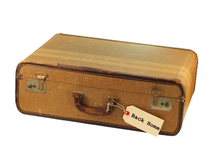 A grungy old brown suitcase with a label saying Back Home isolated on white with a clipping path