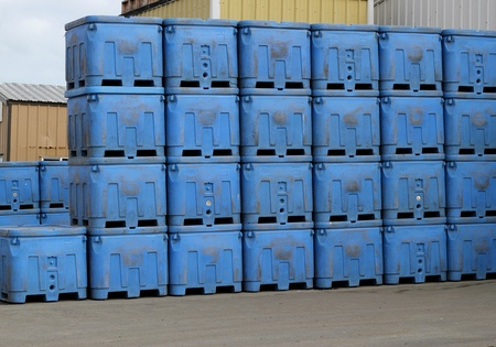 Stacks of bright blue industrial shipping containers outside a fish processing company near the docks Stock Photo