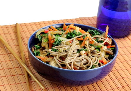 A closeup of a healthy meal of buckwheat soba noodles and colorful stir fried vegetables in a blue bowl on a bamboo mat with chopsticks Stock Photo