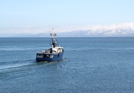 Alaskan commercial fishing boat heading out to sea on a bright sunny day with the Kenai Mountains in the background Archivio Fotografico