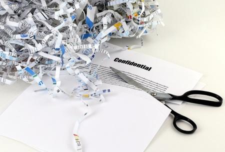 가위로 잘라되는 기밀 문서 옆에 갈가리 찢어진 사무실 용지의 힙