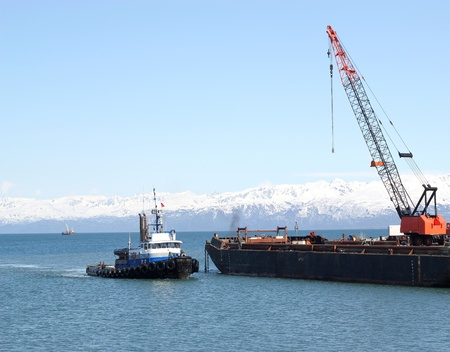 tug boat: A tug boat pulling into an industrial shipping yard with a crane in Alaska with a bright blue sky