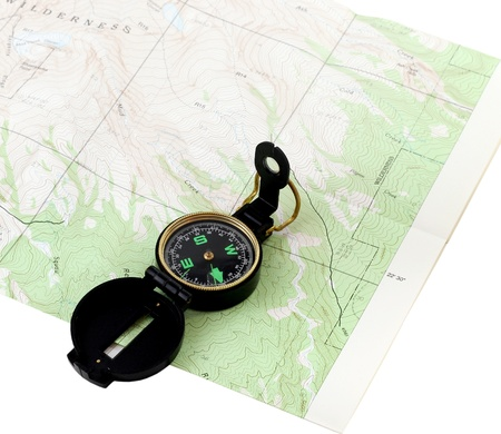 A black navigational compass on a wilderness topo map isolated on white