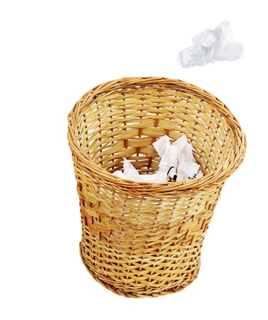 A crumpled paper being thrown into a wicker trash can isolated on a white background