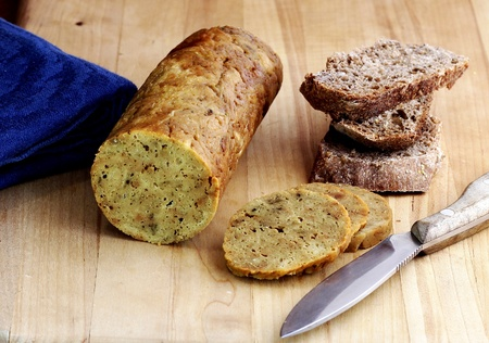 A healthy vegan snack: A roll of vegan seitan on a cutting board with slices of rye bread