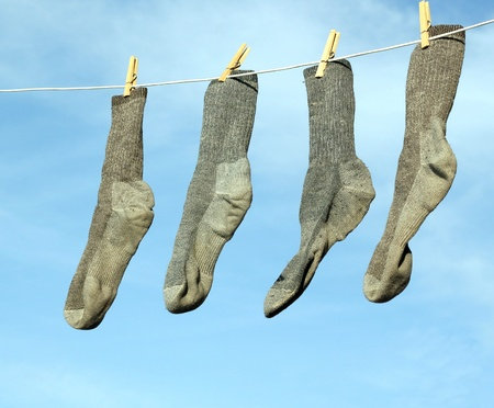 gray socks hanging on a clothesline with a blue sky in the background Stock Photo