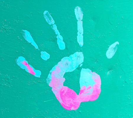 Empreinte de main coloré : une empreinte de main de peinture sur un mur vert Banque d'images - 9678540