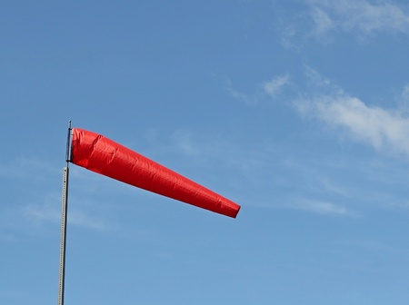 gusty: Bright red windsock blowing in the breeze Stock Photo