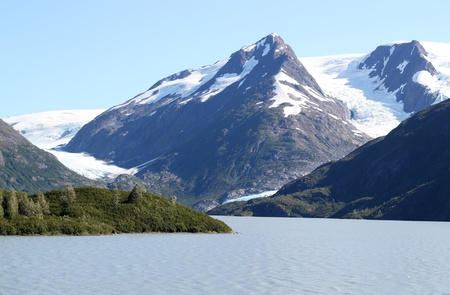 Byron glacier in Alaska with portage lake below it on a sunny summer day