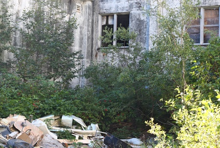 encroaching: Abandoned cement army building with pile of rusting junk and encroaching vegetation Stock Photo