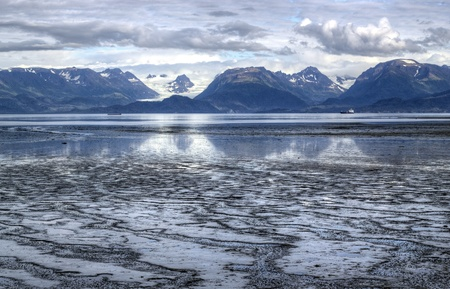 mud and snow: Mud Bay in Alaska at low tide with a Kenai Mountain glacier in the background, reflections in the water, and puffy clouds.