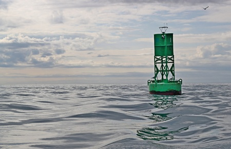 Green navigational buoy in the sea with small waves and cloudy skies.