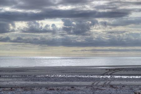 huellas de neumaticos: Playa al atardecer con nubes dram�ticas y visibles huellas de neum�ticos en la arena.