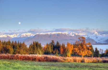 Moon rising over the Kenai mountains with fall colors and warm evening light. Stock Photo