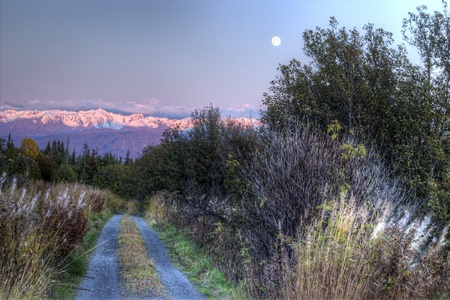 Rural dirt road at sunset with a full moon rising over snow covered mountains.
