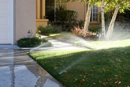 Sprinklers watering the grass and running onto the sidewalk of a typical American tract house