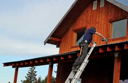 Man on a ladder performing repairs to a metal roof.