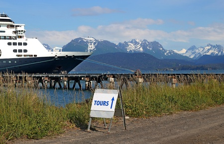 Tour sign for cruise ship passengers with the cruise ship in the background in Homer, Alaska on a sunny day.