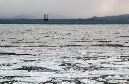 Icy bay in Alaska on a gray day with a jack-up oil drilling rig in the background. photo