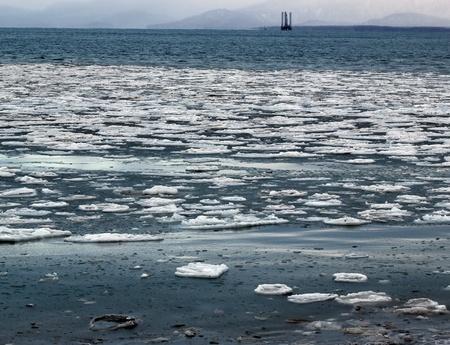 백그라운드에서 잭 - 최대 석유 시추 장비와 알래스카 만의 푸른 물에 떠있는 얼음의 큰 덩어리.