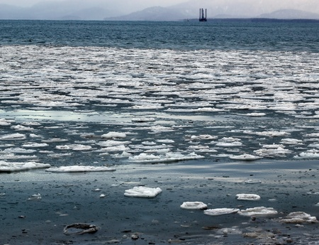 Large chunks of ice floating in blue water of an Alaskan bay with a jack-up oil drilling rig in the background.