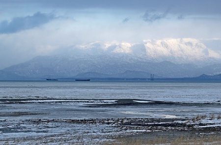Kenai mountains rising above the Kachemak Bay in Alaska in winter with ice forming near the beach and a jackup rig and large shipping barges in the background.