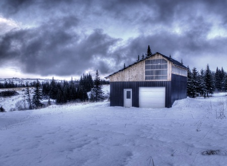 Rural barn on a stormy evening in winter with snow and interesting clouds. photo