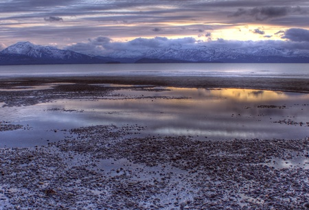 homer: Colorful reflections in tidal pools on a beach off the Kachemak Bay in Homer, Alaska at sunset in winter.