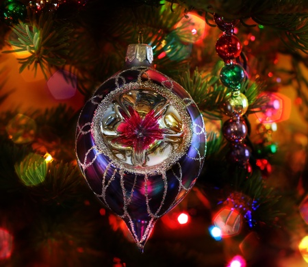 Vintage Christmas ornament handing on the tree with colorful lights forming bokeh patterns. Stock Photo