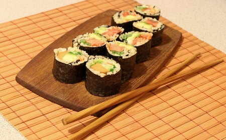 Brown rice sushi rolls on a wooden plate with chop sticks on a bamboo mat. Banco de Imagens - 11773611