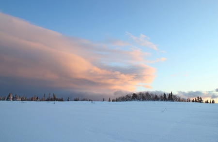 Large sweeping cloud at sunset on a winter day in Alaska with snow in the foreground. photo