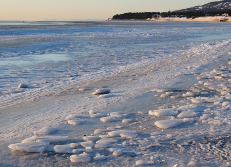 View down icy beach in Homer Alaska with the water and a spit of land in the background.
