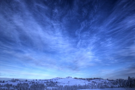 Bright blue sky with streaming clouds in winter with snow covered Alaskan hills.