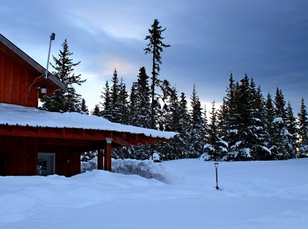 Rural Alaskan house buried in snow with a snow shovel and spruce trees in the background. Stock Photo