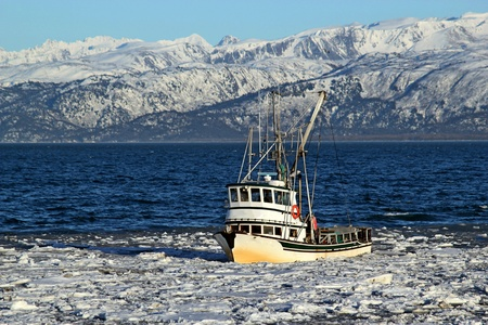 Classic fishing boat traveling through ice in the Kachemak bay near Homer, Alaska with the Kenai mountains in the background on a sunny winter day. Stock Photo