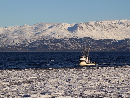 Trawler fishing boat moving through icy water in Alaska on a sunny day with the Kenai Mountains in the background. photo
