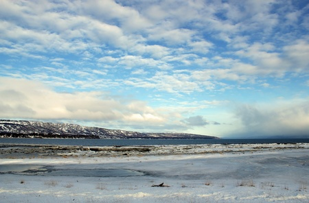mud and snow: Mud bay near Homer, Alaska in winter with ice, snow and interesting cloud patterns. Stock Photo