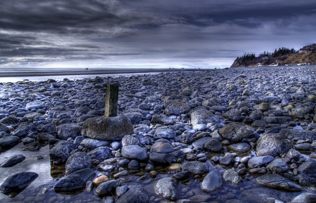 Rocky beach in Alaska with storm clouds and calm water in the background.
