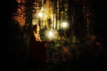 テクスチャ レイヤーで作成された光の白熱球を持つフォレストでケープをはおった女性とファンタジーのシーン。 写真素材