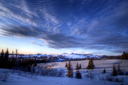 Streaming clouds in the evening sky in rural Alaska in winter. Stock Photo
