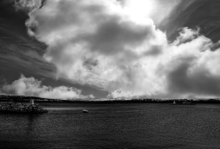 Seascape with dramatic clouds and a large tanker ship leaving the harbor in black and white photo