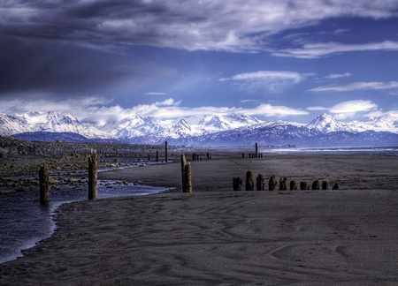 homer: Old pier pillars on an Alaskan beach near Homer Alaska on a sunny day with clouds and the Kenai Mountains in the background.