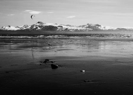 Kite surfer on an Alaskan beach at low tide near Homer Alaska in black and white.