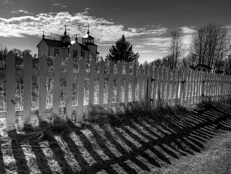Dramatic fence shadows with the Russian orthodox church in Nikiski Alaska in black and white. Banco de Imagens