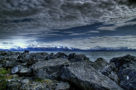 homer: Large pile of rocks forming the sea wall on the Homer Spit with a view of the Kachemak Bay in Alaska with interesting clouds and snow covered mountains in the background.