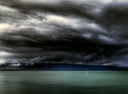 sheltering: Dark storm clouds over the Kachemak bay with a small sailboat sheltering from the storm.