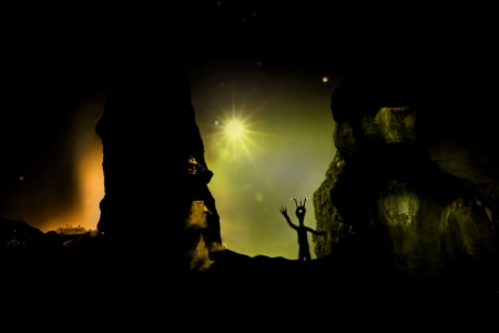 Digital illustrations of a friendly alien with multiple eyestalks waving beside rock formations on a strange planet.