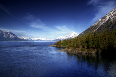 inlet bay: View of the water of the Turnagain Arm near Hope Alaska in soft evening light with bright blue skies.